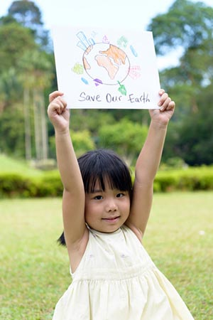 Young girl holding up sign to save our planet